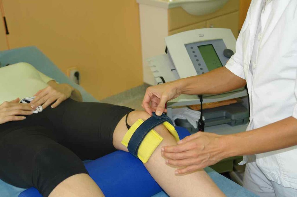 Fizioterapevt pritrdi blazinice s trakom da se izvaja elektroterapija