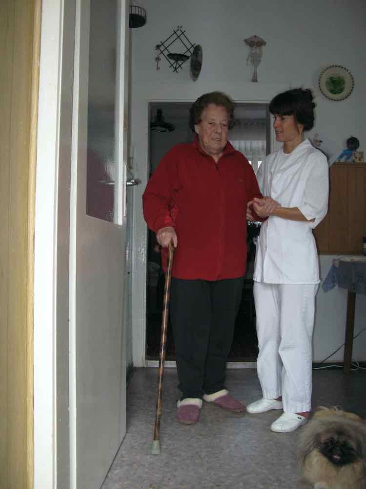 Stara mama se s pomocjo fizioterapevta trudi peljati psa ven