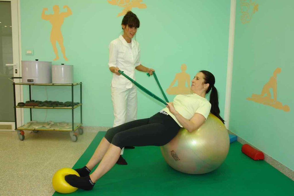 Pacient z elastiko krepi rotatorno manšeto medtem ko ima nasmeh na obrazu