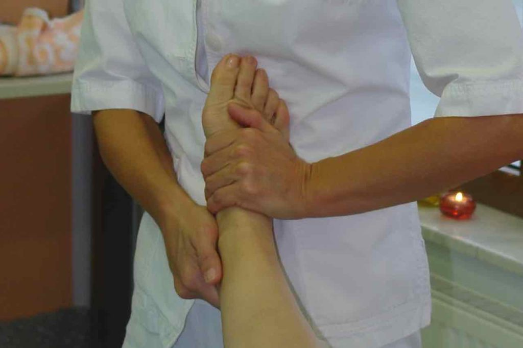 stopalo je naslonjeno na fizioterapevta med refleksno masazo stopal