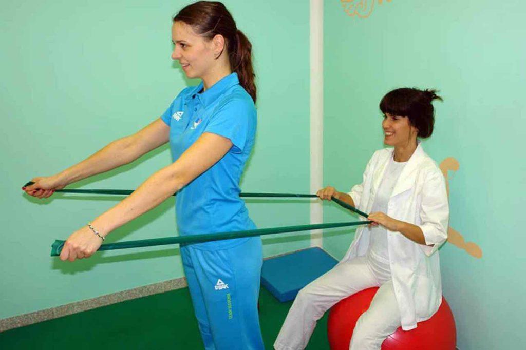 Fizioterapevtka in olimpijska sportnica se zabavata med športno fizioterapijo.